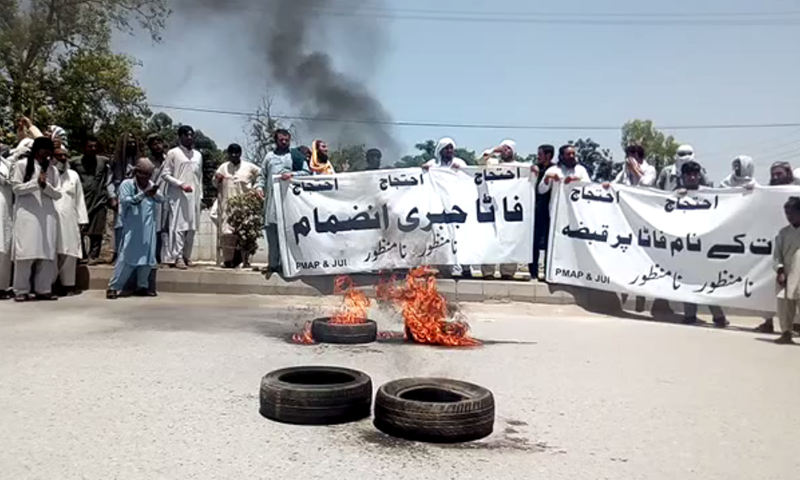 Protesters holding banners outside the KP Assembly. — DawnNewsTV