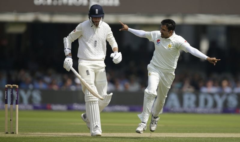Mohammad Abbas celebrates after taking the wicket of England's Stuart Broad caught behind left who walks from the pitch during the fourth day of play of the first test cricket match between England and Pakistan at Lord's cricket ground in Londo