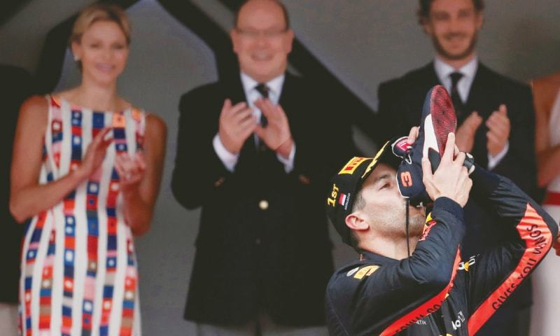 DANIEL Ricciardo of Red Bull drinks out of his shoe as he celebrates winning the Monaco F1 Grand Prix on Sunday.—Reuters