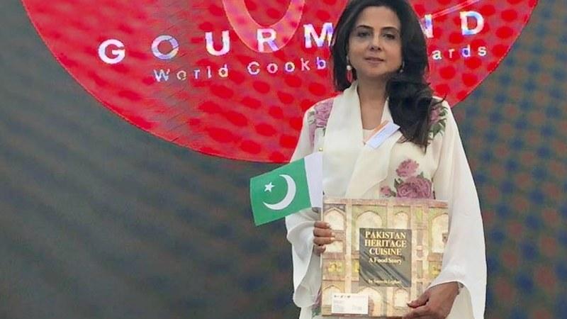 Author Sayeeda Leghari holds up the Pakistani flag along with her award-winning book at the 2018 Gourmand World Awards — Publicity photo