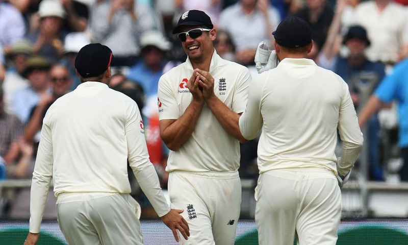 Alastair Cook celebrates with teammates after making the catch to take the wicket of Asad Shafiq. —AFP