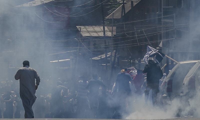 Men carry the body of Qaiser Amin Bhat amid tear gas smoke fired by Indian forces after they stopped the funeral procession. — AP