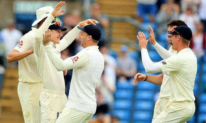 England's Dominic Bess (2L) celebrates with teammates after making the catch off the bowling of England's James Anderson to take the wicket of Pakistan's Haris Sohail for 8 on the third day of the second Test cricket match between England and Pakistan at Headingley cricket ground in Leeds, northern England on Sunday. — AFP