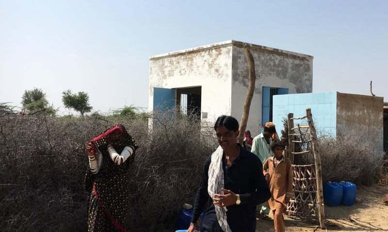 مقامی افراد آر او پلانٹ سے پانی لے رہے ہیں — فوٹو: حنیف ساموں