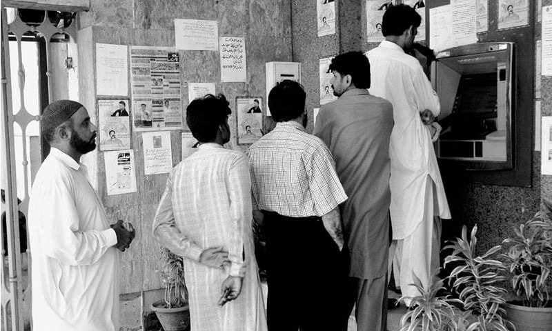 People standing in queue to withdraw cash from an ATM outside a bank branch. At the end of 1QCY18, the number of ATMs across the country reached 13,835 and processed transactions worth Rs1.4tr, reducing the load on conventional banking.