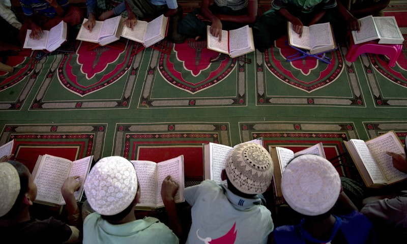 Rohingya refugee children read Quran in a makeshift Mosque in Kutupalong refugee camp near Cox's Bazar, Bangladesh. —AP