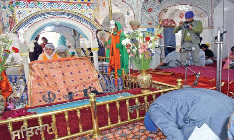 Sikh pilgrims perform their rituals at Gurdwara Punja Sahib on Saturday. — Dawn