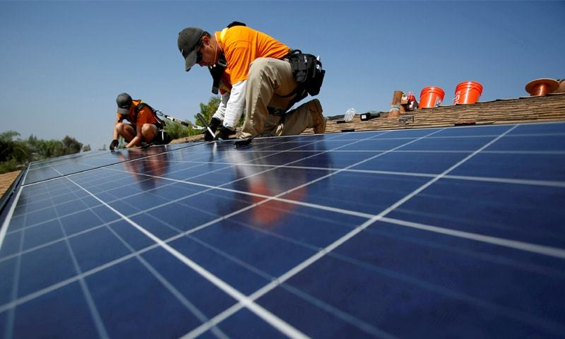 California: Solar technicians install solar panels on the roof of a house in Mission Viejo.—Reuters/file