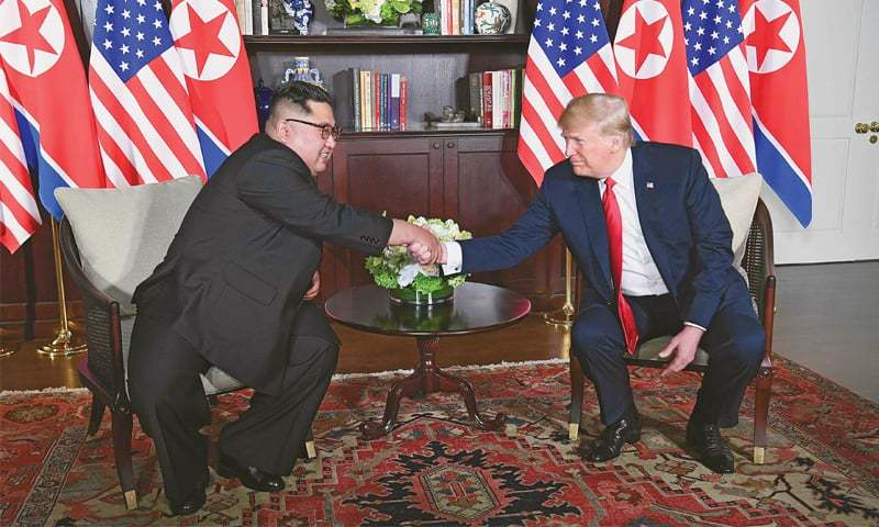 US President Donald Trump shakes hands with North Korea's leader Kim Jong Un as they sit down for their historic summit in a hotel on the Sentosa island in Singapore on Tuesday.—AFP