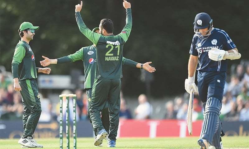 EDINBURGH: Mohammad Nawaz (centre) celebrates taking the wicket of Scotland's captain Kyle Coetzer on Tuesday.—AFP