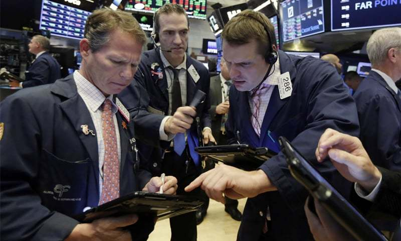 Traders Robert Charmak, left, Gregory Rowe, center, and Michael Milano work on the floor of the New York Stock Exchange, on Wednesday. Stocks opened slightly higher on Wednesday, with investors focused on the approval of AT&T's takeover of Time Warner as well as the Fed statement.­—AP