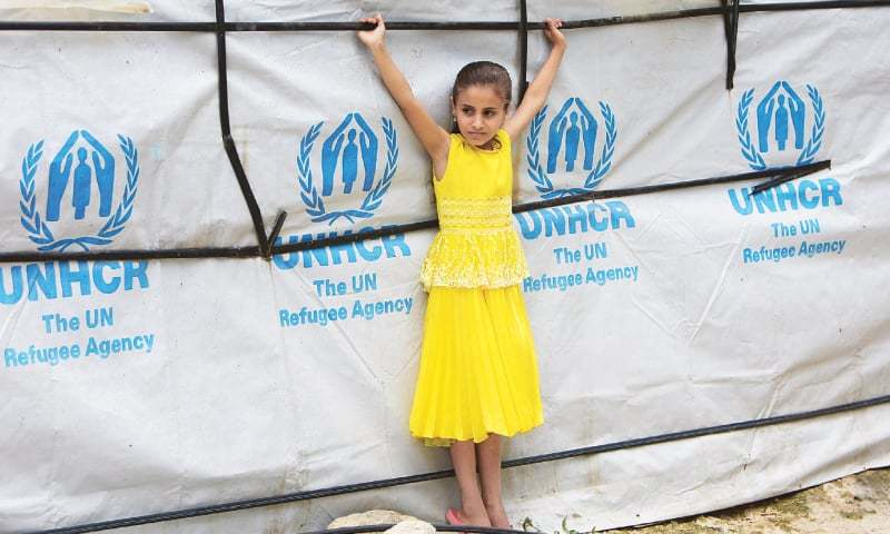 A SYRIAN refugee girl stands outside a tent at a refugee camp in Zahrani town, Lebanon, on Wednesday.—Reuters