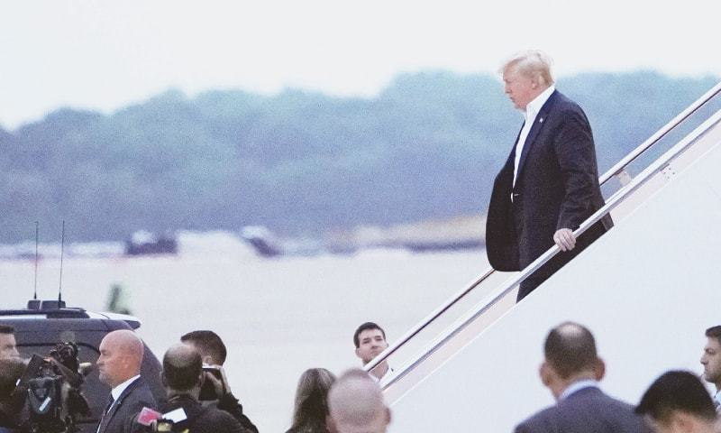 US President Donald Trump steps off Air Force One upon arrival at Andrews Air Force Base in Maryland on Wednesday, after attending the US-North Korea Summit in Singapore.—AFP