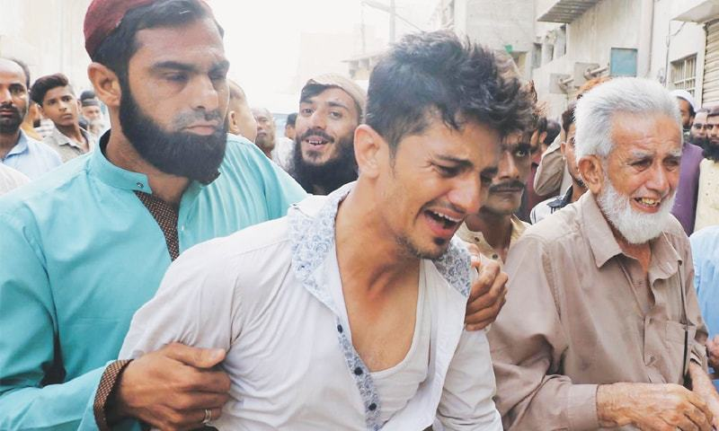 A RELATIVE reacts to the grim news outside the family's residence in Lyari on Friday.—Online