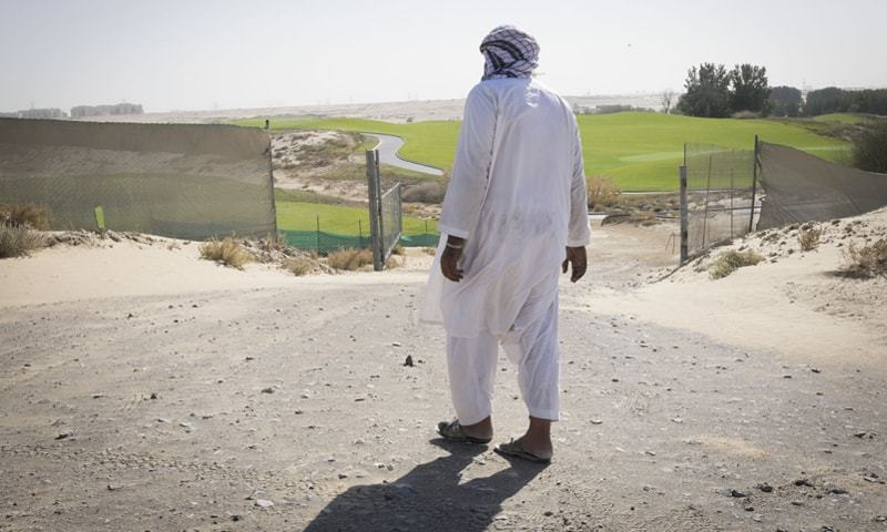 A migrant workers walks towards a golf course in Dubai.—Bloomberg
