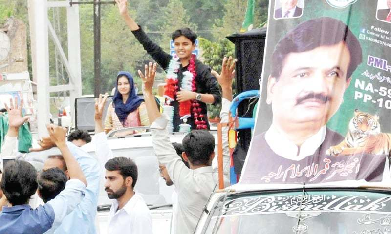 Detained PML-N candidate's children wave to party workers before filing their father's nomination papers. — Online