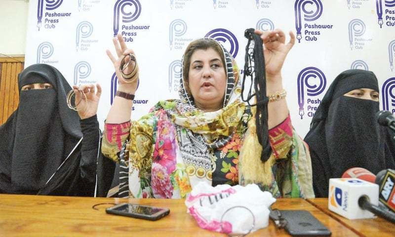 PTI former MPA Zareen Zia shows bangles and braid tassels during a press conference in Peshawar. — White Star