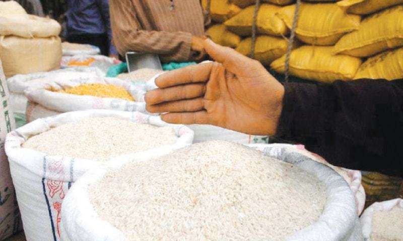 The image shows a shopkeeper pointing towards mounds of rice in his shop. According to the Pakistan Bureau of Statistics, Pakistan exported 3.84m tonnes of both basmati and non-basmati rice for $1.89bn from July 2017 to May 2018.—Dawn file photo