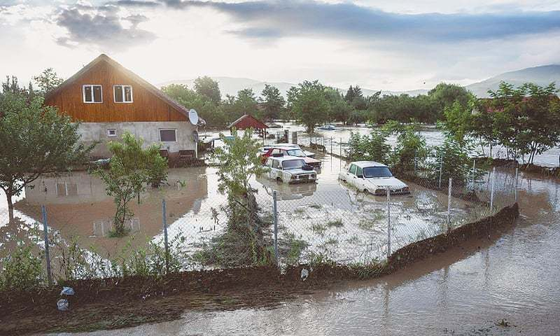 BACEL (Romania): Parked cars covered in floodwater on Sunday morning.—AFP