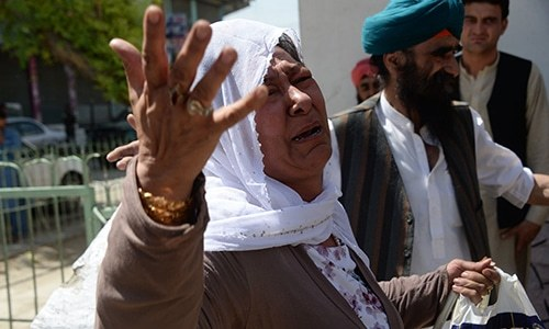 An Afghan Sikh woman weeps during a burial ceremony following a suicide attack in Jalalabad. — AFP