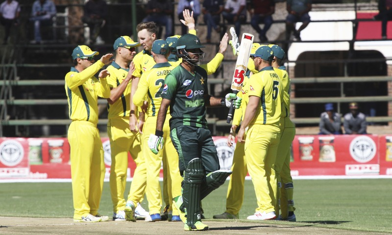 Australian cricket players celebrate the wicket of Pakistan batsman Muhammad Hafeez center as he walks off the pitch during the T20 cricket match at Harare Sports Club Monday. — AP