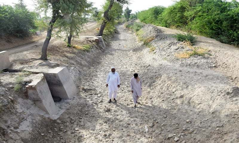 Villagers walk on a dried up canal near Badin, fed by the Kotri Barrage. Water flows have dried up, devastating the Kharif planting season.