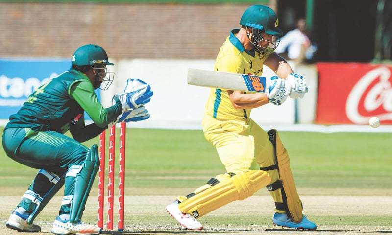 HARARE: Australian captain Aaron Finch plays a shot as Pakistan skipper Sarfraz Ahmed looks on during the second match of the T20 tri-series at the Harare Sports Club on Monday.—AFP