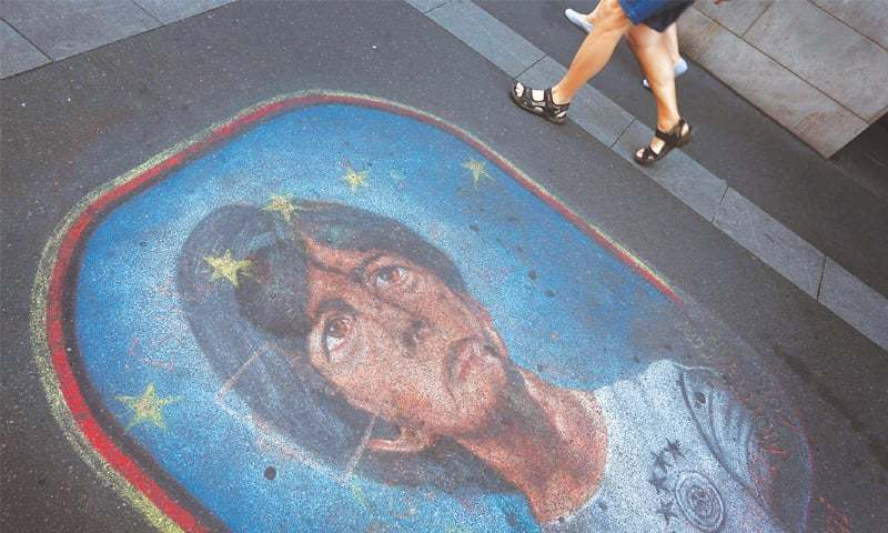 PEDESTRIANS in Wuerzburg on Tuesday walk past a pavement painting that depicts Joachim Loew.—AFP