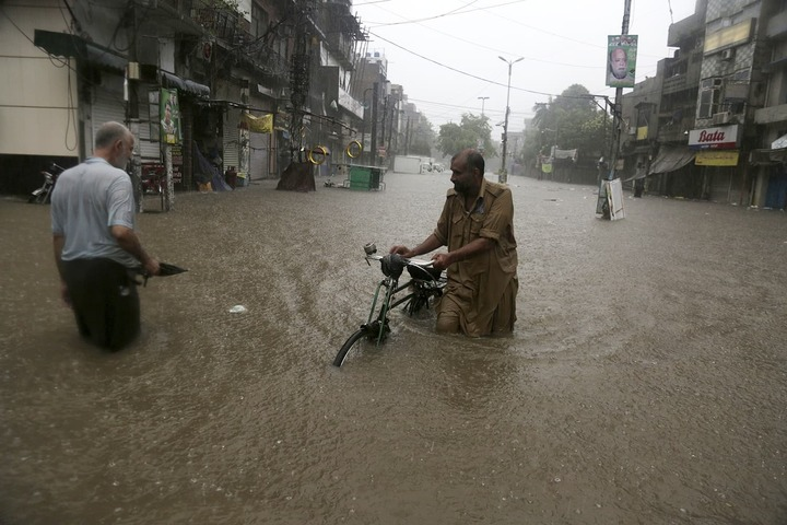 People wade through a flooded road after heavy rain fall in Lahore on Tuesday. — AP