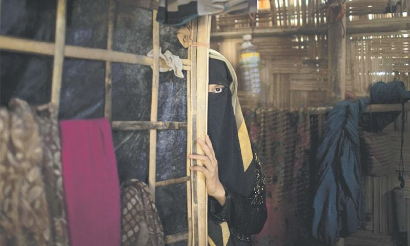 """A"", a 13-year-old Rohingya Muslim girl, peers from behind a partition in her family's shelter in Jamtoli refugee camp in Bangladesh. Two months earlier, soldiers had broken into her home back in Myanmar and raped her.—AP"