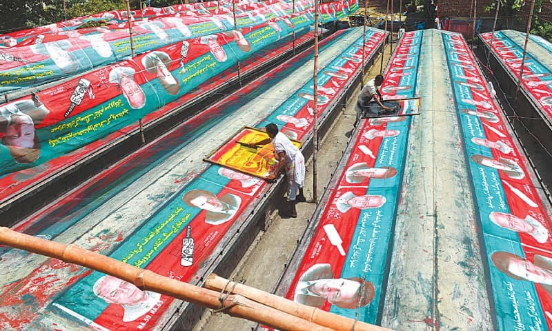 A MAN prepares banners for Pakistan Tehreek-i-Insaf's election campaign in Lahore.—M. Arif / White Star
