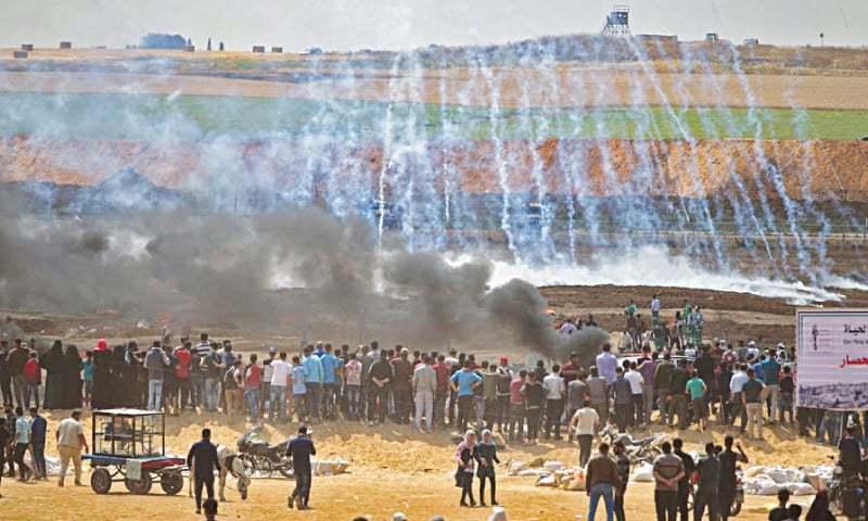 Palestinian protesters face tear gas as smoke billows from burning tyres at Gaza border on May 14, 2018 | AFP