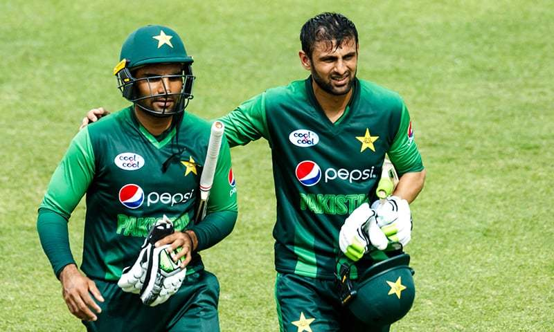 Shoaib Malik with Asif Ali after victory in action during the final of the tri-series — AFP