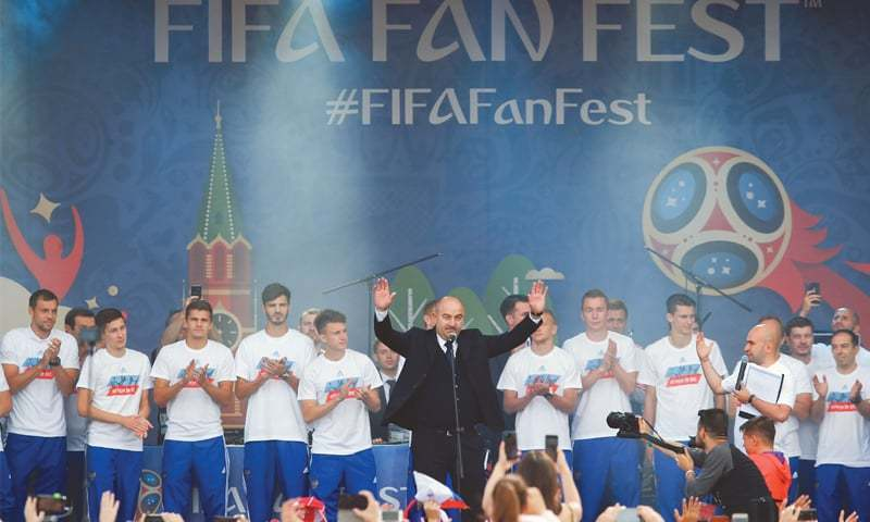 MOSCOW: Russia's coach Stanislav Cherchesov (C) and players are greeted by fans during a visit at the Russian capital's fan zone on Sunday.—AFP