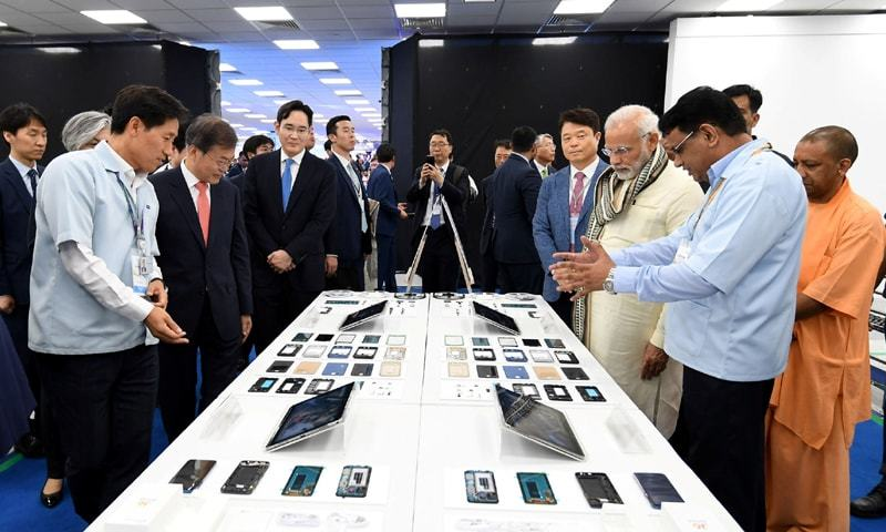 NOIDA: Indian Prime Minister Narendra Modi and South Korean President Moon Jae-in take a tour inside the Samsung Electronics smartphone manufacturing facility after it's inauguration on Monday.—Reuters