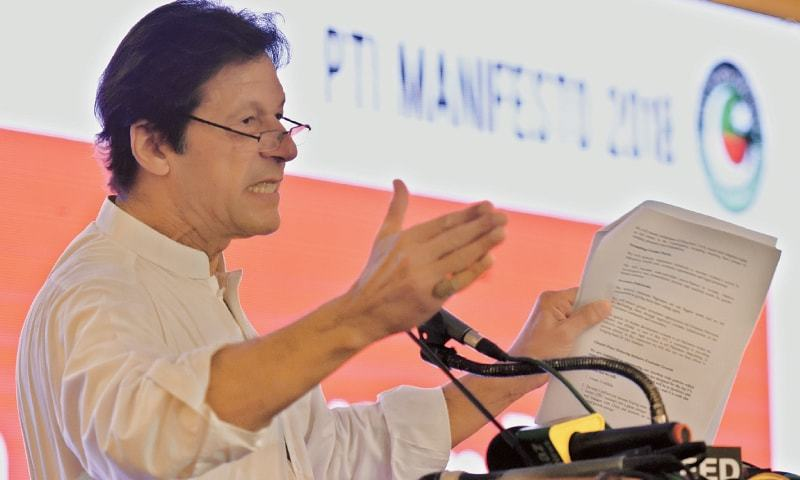ISLAMABAD: Pakistan Tehreek-i-Insaf chairman Imran Khan holds a copy of the party's manifesto for the 2018 general elections at the launch on Monday.—Tanveer Shahzad/White Star