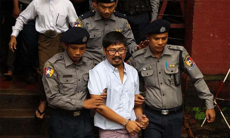 گرفتار صحافی وا لون کو مقدمے سے قبل ہونے والی پیشی میں پولیس کی کڑی نگرانی میں عدالت لایا جارہا ہے—فوٹو: اے ایف پی