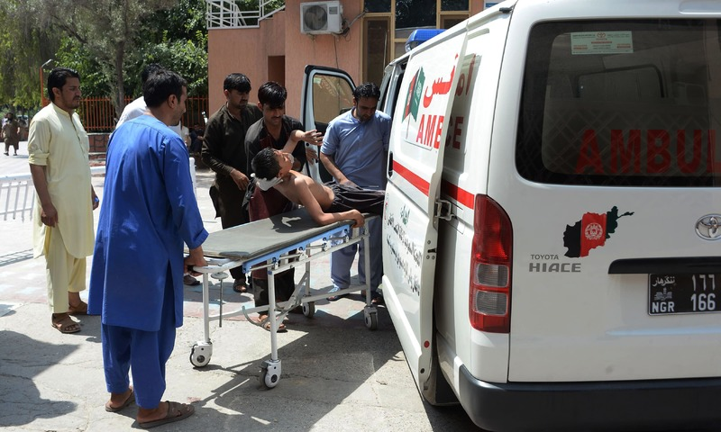 Afghan volunteers carry an injured youth on a stretcher to a hospital following an attack that targeted an education department compound in Jalalabad on July 11, 2018. — AFP