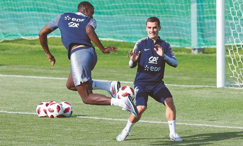 MOSCOW: France's Paul Pogba (L) performs a trick with the ball as team-mate Antoine Griezmann looks on during a practice session on Thursday.—Reuters