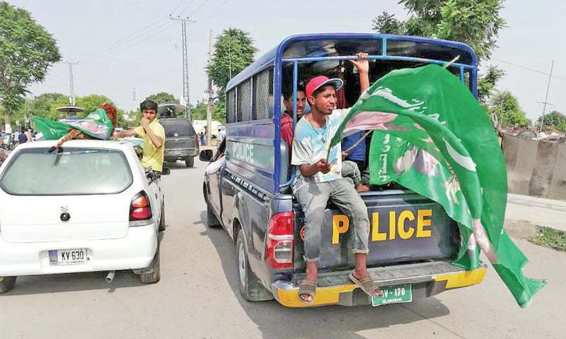 A PML-N worker waves party flag while sitting in a police van. — Dawn