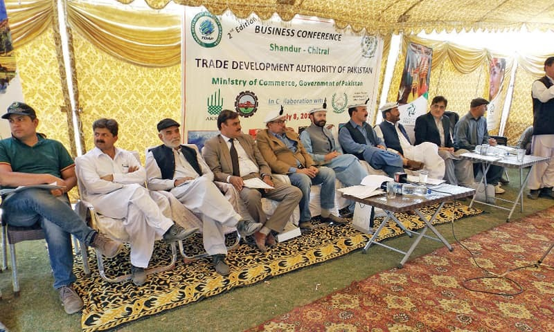 Speakers sit on the stage during the business conference in Shandur on Thursday. — Dawn