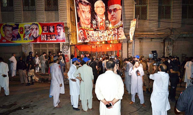 People are gathered at the site of a suicide attack on an ANP corner meeting in Peshawar that killed at least 21 people on Tuesday. — APP