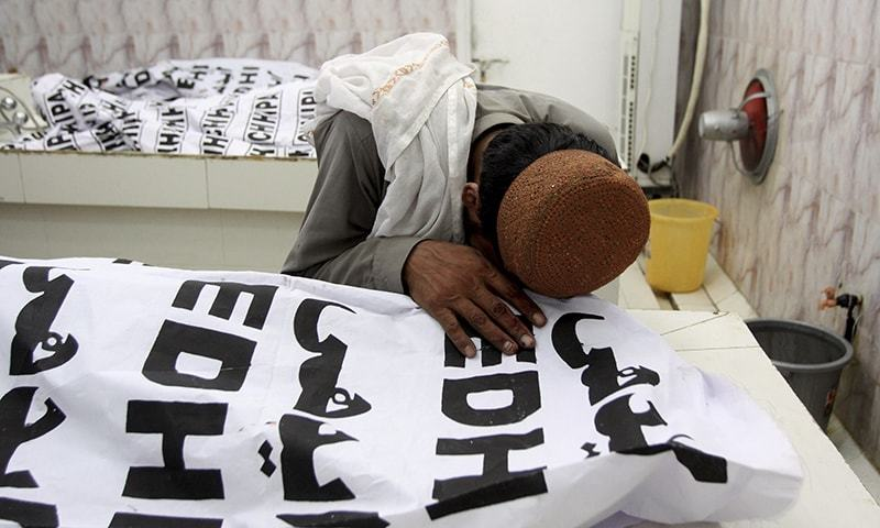 A man mourns over a dead body of his family member who was killed in the bomb attack, at a mortuary in Quetta on Friday. — AP