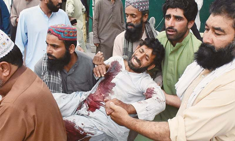 PEOPLE shift one of the injured to a hospital in Quetta on Friday.—Reuters