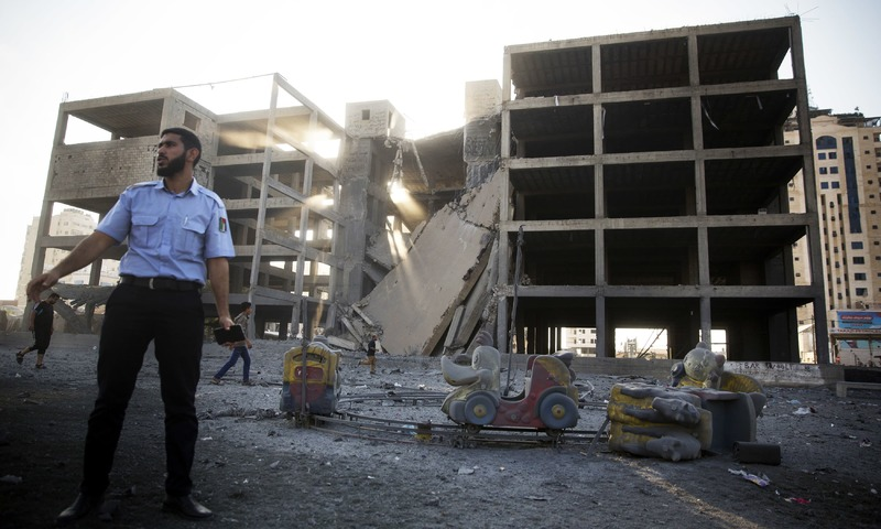 A Palestinian policeman guards next to a destroyed building following an Israeli airstrike in Gaza City. —AP