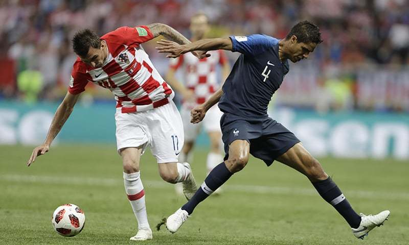 Croatia's Mario Mandzukic and France's Raphael Varane battle for the ball. —AP