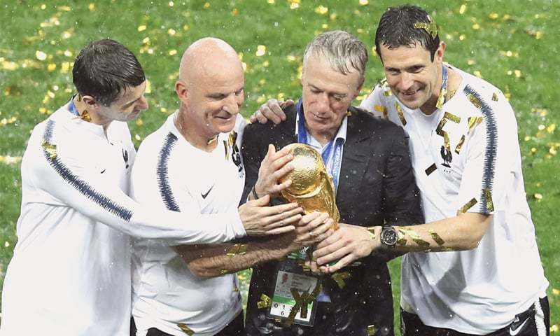 FRENCH coach and 1998 World Cup-winning captain Didier Deschamps (second R), holds the trophy at the post-final presentation ceremony.—AP