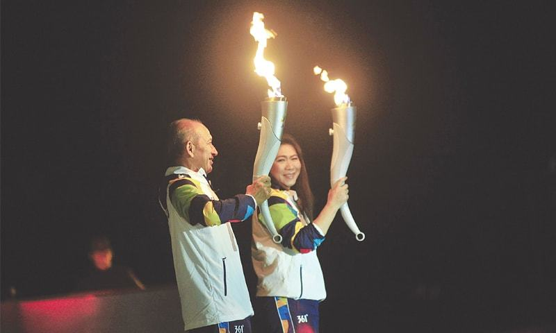 INDONESIAN former tennis and badminton players Yustedjo Tarik (L) and Susi Susanti carry the flames from Indonesia and India, respectively.—AFP