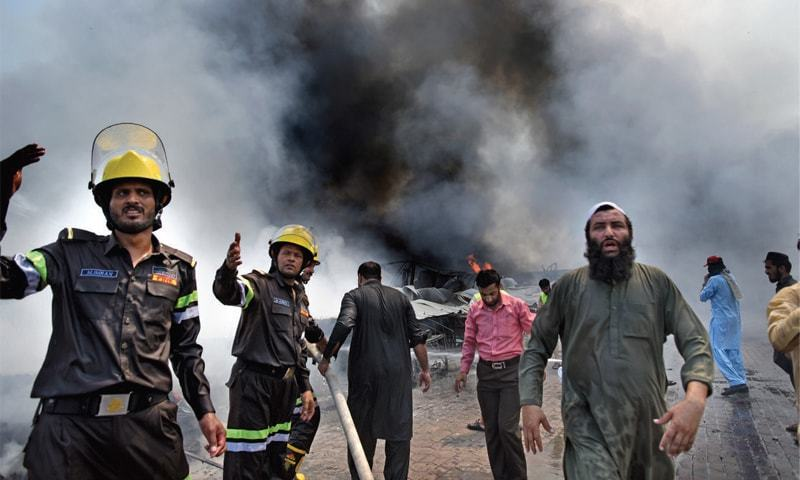 Firefighters gesture as they extinguish fire at the weekly bazaar in Islamabad on Wednesday. — Photo by Tanveer Shahzad