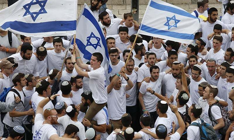 In this May 13, 2018, file photo, Israeli youths wave national flags outside the Old City's Damascus Gate, in Jerusalem. —AP
